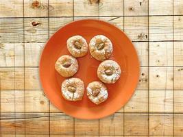 biscotti su un piatto arancione su uno sfondo di tavolo in legno foto