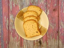 pane a fette su un piatto di ceramica su uno sfondo di tavolo in legno foto