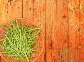 fagioli verdi su un piatto di vimini su uno sfondo di tavolo in legno foto