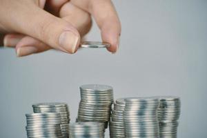 mano della donna che mette le monete d'argento dei soldi da impilare foto