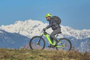 giovane durante l'escursione in mountain bike sulla collina foto