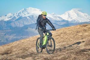 uomo in bicicletta su una montagna foto