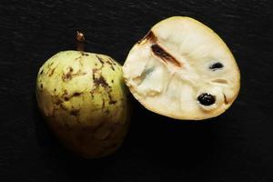frutta cherimoya tagliata a metà su sfondo di ardesia foto