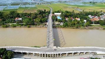 bekasi, indonesia 2021 - veduta aerea con drone di un lungo ponte alla fine del fiume che collega due villaggi foto