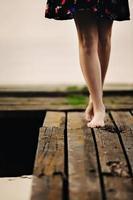 primo piano di una donna che cammina a piedi nudi su un ponte foto