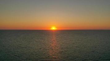 sole che tramonta dietro la linea dell'orizzonte foto
