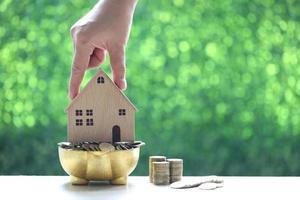 pila di monete in legno salvadanaio e casa modello su sfondo verde naturale
