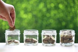 mano della donna che mette una moneta nella bottiglia di vetro su priorità bassa verde