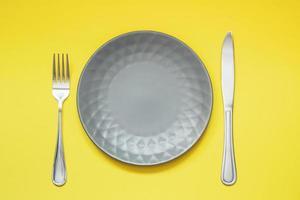 piatto grigio vuoto e posate su sfondo giallo foto
