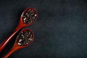 mix di pepe rosso e nero in cucchiaio di legno su sfondo nero foto