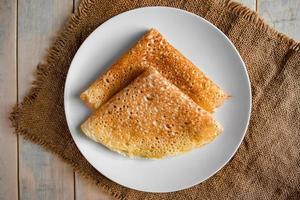 frittelle su un piatto bianco su uno sfondo di lino foto