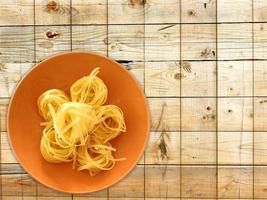 pasta su un piatto arancione su uno sfondo di tavolo in legno foto