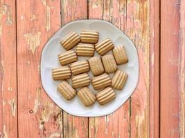 biscotti a strisce su un piatto bianco su uno sfondo di tavolo in legno foto