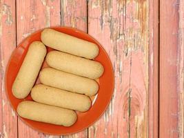 biscotti su un piatto rosso su uno sfondo di tavolo in legno foto