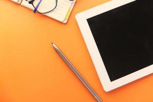 tavoletta digitale e stilo su sfondo arancione foto