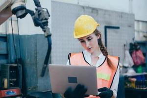 donna che tiene un computer portatile in un cantiere edile foto