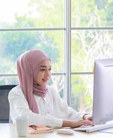 bella imprenditrice musulmana che lavora felicemente in ufficio foto
