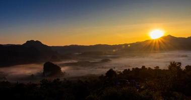 il sole sorge sulle montagne e sulla nebbia foto