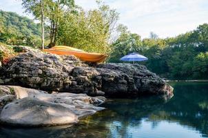 kayak arancione e ombrello blu vicino al fiume nella foresta foto