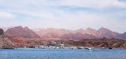barche da crociera vicino a una costa rocciosa foto