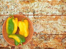 peperoni verdi e gialli su un piatto di vimini su uno sfondo di tavolo in legno foto