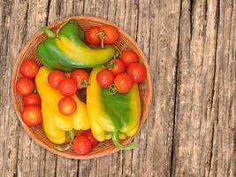 peperoni e pomodori verdi e gialli su un piatto di vimini su uno sfondo di tavolo in legno foto
