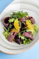 insalata di erbe condita con fette di arancia e prosciutto foto