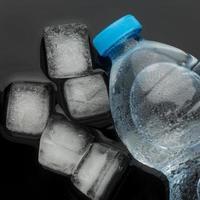 cubetti di ghiaccio e acqua in bottiglia, vista frontale foto