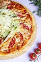 pizza condita con formaggio e basilico extra foto