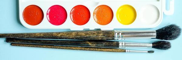 scatola di colori ad acquerello e pennelli per disegnare su sfondo blu foto