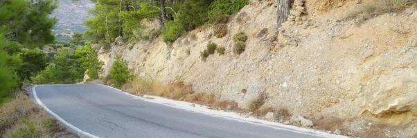 strada asfaltata nelle montagne mediterranee ricoperte di alberi di pino foto