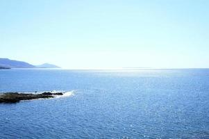 paesaggio marino con montagne e rocce all'alba, bella acqua blu e cielo foto