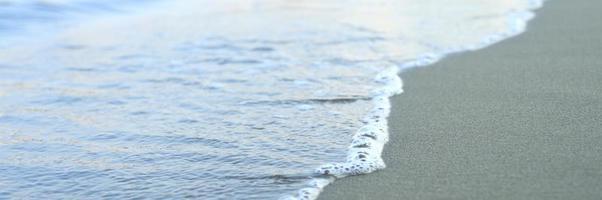 onda sfocata del mare sulla spiaggia di sabbia di sera foto