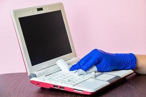 disinfezione e pulizia del laptop e delle superfici domestiche su sfondo rosa foto