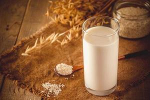 bicchiere di latte d'avena su uno sfondo di legno foto