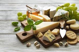 vari tipi di formaggio su uno sfondo bianco di legno foto