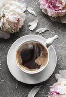 fiori di peonia rosa e una tazza di caffè foto