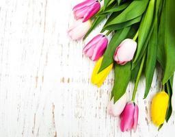 bouquet di tulipani rosa e gialli su uno sfondo di legno foto