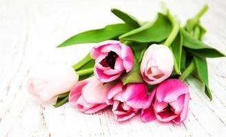 bouquet di tulipani rosa su un vecchio sfondo di legno foto