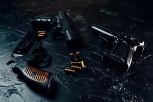 tre pistole e proiettili sulla tavola nera foto