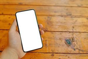 mano d'uomo tiene smartphone su un tavolo di legno foto