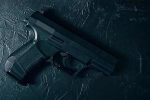 pistola sul tavolo texture di cemento verde foto