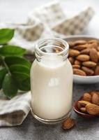 bottiglia di vetro con latte di mandorle e mandorle sul tavolo foto