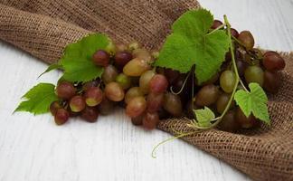 uva con foglie su un vecchio sfondo di legno foto