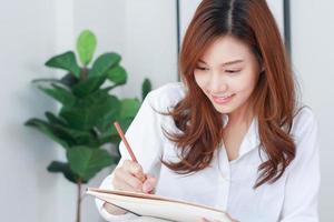 la donna asiatica di affari scrive le informazioni di marketing