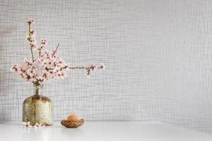 decorazione sul tavolo della cucina con margherite primaverili, uovo di Pasqua e uno spazio vuoto bianco foto
