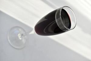 piccolo bicchiere di vino rosso su uno sfondo bianco con le ombre foto