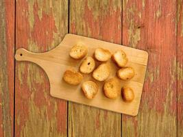 toast a fette su un tagliere di legno su uno sfondo di tavolo in legno foto