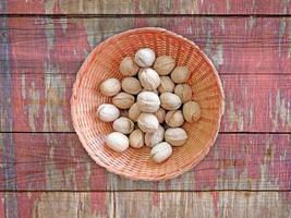 noci intere in una ciotola di vimini su uno sfondo di tavolo in legno foto