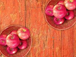 mele rosse su un piatto di vimini su uno sfondo di tavolo in legno foto
